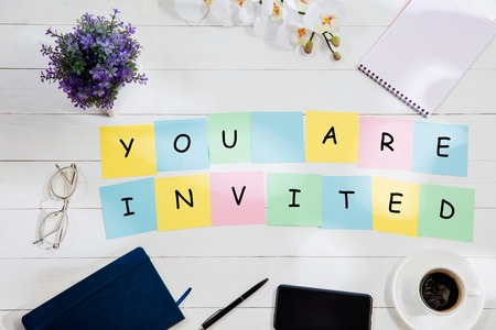 YOU ARE INVITED. Message at colorful note papers on a desk background. Lifestyle, business, office, motivation, plan, success, goal and management concept. Top or flat lay view. Stock Photo