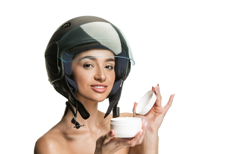 Portrait of attractive woman in motorbike helmet on white studio background. Beauty and skin protection concept