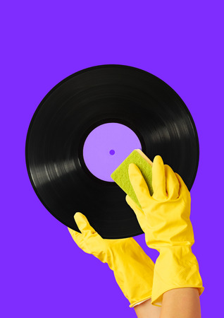 How to make a clean sound. Hands in yellow housewifely glove with the sponge cleaning black vinyl record against purple background. Music concept. Modern design. Contemporary art collage. Stockfoto