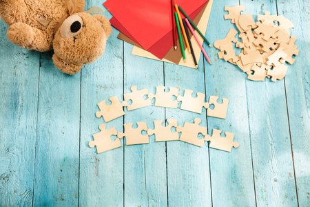 Concept of mock up and pieces of puzzles on the background of wooden table. Education, school, family, baby, pregnancy, maternity, parenting, children concepts