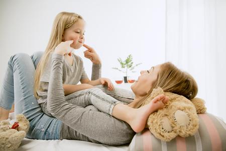 Giovane madre e la sua piccola figlia a casa al mattino soleggiato. Colori pastello tenui. Buon tempo in famiglia nel fine settimana. Concetto di festa della mamma. Concetti di famiglia, amore, stile di vita, maternità e momenti teneri.