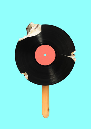 An alternative icecream. Meloman wanna bite a piece of immortal music. Vinyl record formed icecream on a wooden stick against blue sky colored background. Modern design. Contemporary art collage.