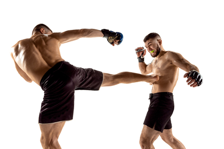 MMA. Two professional fightesr punching or boxing isolated on white studio background. Couple of fit muscular caucasian athletes or boxers fighting. Sport, competition, excitement and human emotions concept