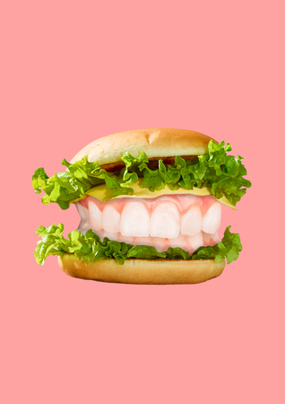 An alternative burger. It tastes so delicious. A hamburger with salad, cheese and white teeth as a meat against light background. Food concept. Contemporary pop design. Modern art collage.