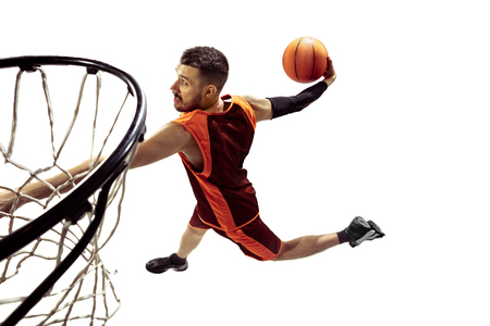Full length portrait of a basketball player with ball isolated on white background. Advertising concept. Fit caucasian athlete jumping at studio and throwing the ball into the basketball hoop. Motion, activity, movement concepts.
