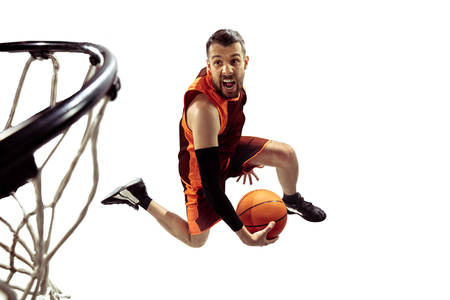 Full length portrait of a basketball player with ball isolated on white background. Advertising concept. Fit caucasian athlete jumping at studio and throwing the ball into the basketball hoop. Motion, activity, movement concepts. Reklamní fotografie