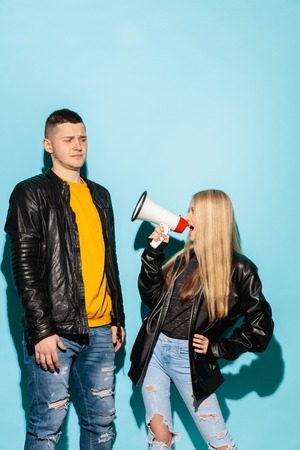 Portrait of young female student in denim clothes holding megaphone and screaming against blue studio background. Two teen friends - man and girl with serious emotion. Education in high school concept. Copy space Foto de archivo