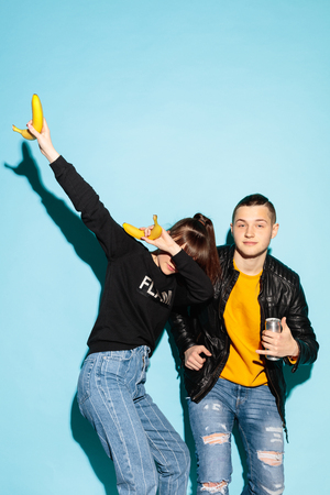 Cool party. Close up fashion portrait of two young hipster girl and boy wearing jeans wear. Studio shot of two models having fun together. Woman making a dab movement with arms. Human emotions concept 免版税图像