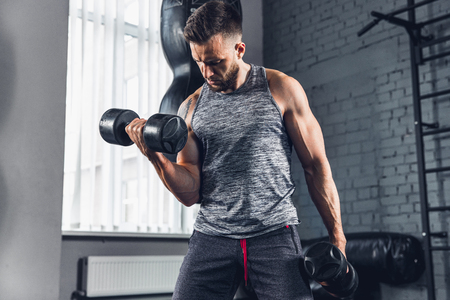 Get better. The athlete trains in the gym, doing strength exercises for muscles, triceps and biceps, work on upper body with weights and dumbbells. Fitness, healthy, sport and self-control concept.