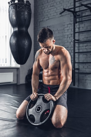 In control. The athlete trains in the gym, doing strength exercises for different groups of muscles, work on his upper body with weight and barbells. Fitness, sport, healthy and self-control concept.