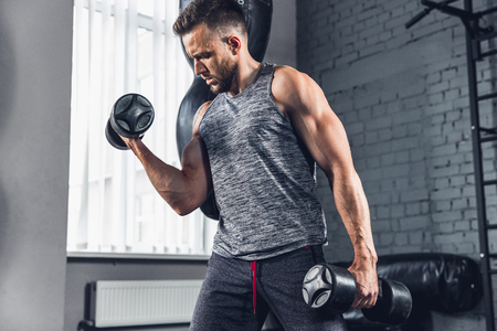 One step closer. The athlete trains in the gym, doing strength exercises for muscles, triceps and biceps, work on his upper body with weights and dumbbells. Fitness, healthy and self-control concept. Stok Fotoğraf
