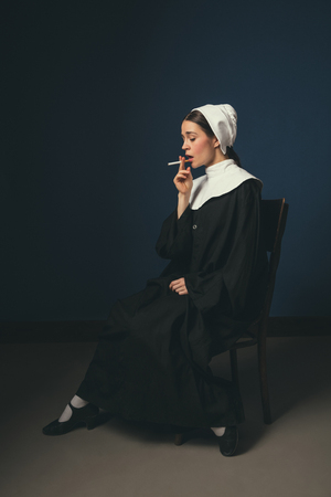 A little devilment. Medieval young woman as a nun in vintage clothing and white mutch sitting on the chair on dark blue background. Smoking cigarette in secret. Concept of comparison of eras.