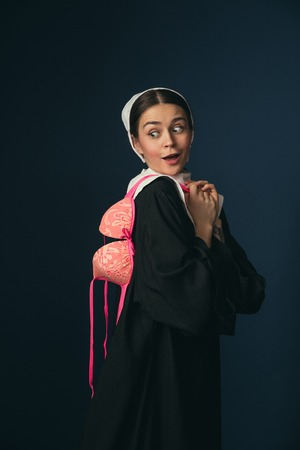 A mad antic in a big antique. Medieval young woman in black vintage clothing and mutch as a nun standing on dark blue background. Trying on bright pink bra. Concept of comparison of eras.