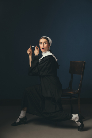 Breaking news. Medieval young woman as a nun in vintage clothing and white mutch sitting on the chair on dark blue background. Smoking cigarette in secret. Concept of comparison of eras.