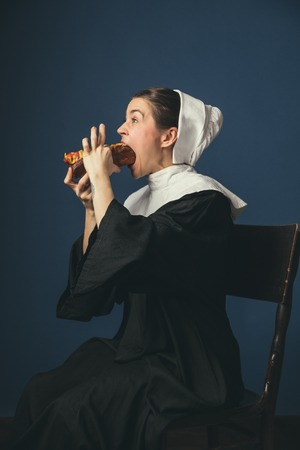 Believe in yourself - you can do more. Medieval young woman as a nun in vintage clothing and white mutch sitting on the chair on dark blue background. Eating hot dog. Concept of comparison of eras.