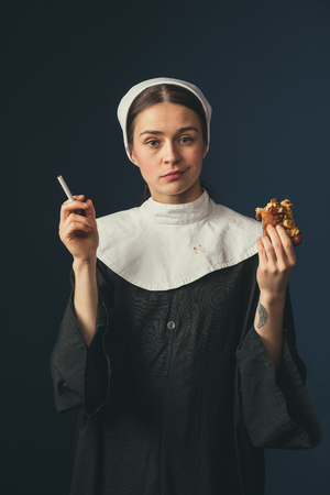 Choose the best one. Medieval young woman as a nun in vintage clothing sitting on the chair on dark blue background. Smoking cigarette and eating hot dog in secret. Concept of comparison of eras. Banque d'images