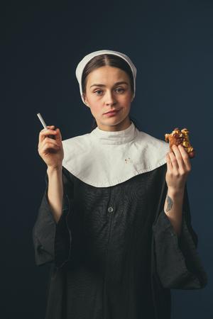Wählen Sie das Beste aus. Mittelalterliche junge Frau als Nonne in Vintage-Kleidung, die auf dem Stuhl auf dunkelblauem Hintergrund sitzt. Zigarette rauchen und heimlich Hot Dog essen. Konzept des Vergleichs von Epochen.