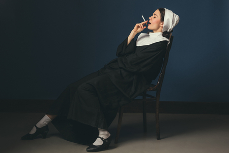 Chill like no one else. Medieval young woman as a nun in vintage clothing and white mutch sitting on the chair on dark blue background. Smoking cigarette in secret. Concept of comparison of eras.
