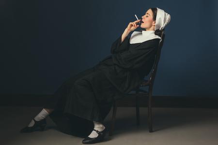 Chillen wie kein anderer. Mittelalterliche junge Frau als Nonne in Vintage-Kleidung und weißem Mutch, die auf dem Stuhl auf dunkelblauem Hintergrund sitzt. Rauchen heimlich Zigarette. Konzept des Vergleichs von Epochen. Standard-Bild