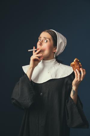 Kümmere dich nicht um Bildung. Mittelalterliche junge Frau als Nonne in Vintage-Kleidung auf dem Stuhl auf dunkelblauem Hintergrund. Zigarette rauchen und heimlich Hot Dog essen. Konzept des Vergleichs von Epochen. Standard-Bild