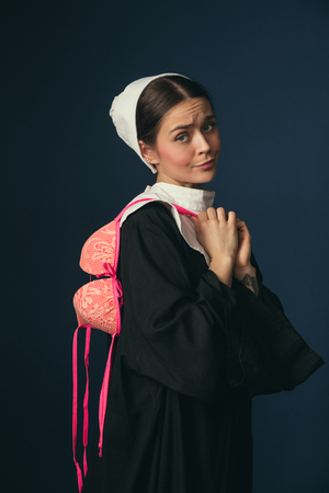 Lets try being a little devilry. Medieval young woman in black vintage clothing and mutch as a nun standing on dark blue background. Trying on bright pink bra. Concept of comparison of eras. Stock Photo