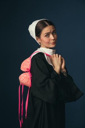 Versuchen wir, eine kleine Teufelei zu sein. Mittelalterliche junge Frau in schwarzer Vintage-Kleidung und Mutch als Nonne, die auf dunkelblauem Hintergrund steht. Anprobieren eines hellrosa BHs. Konzept des Vergleichs von Epochen.