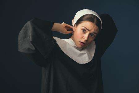 Gemischte Gefühle. Mittelalterliche junge Frau als Nonne in Vintage-Kleidung, weißem Mutch und langen Haaren auf dunkelblauem Hintergrund. Bereite sie auf einen neuen Tag vor. Konzept des Vergleichs von Epochen.