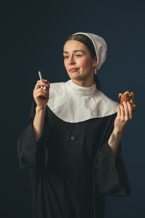 No more problems. Medieval young woman as a nun in vintage clothing sitting on the chair on dark blue background. Smoking cigarette and eating hot dog in secret. Concept of comparison of eras.