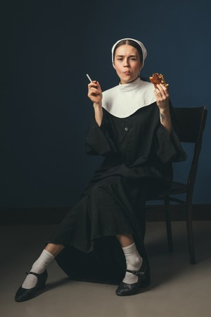 Dont care about the rules. Medieval young woman as a nun in vintage clothing on the chair on dark blue background. Smoking cigarette and eating hot dog in secret. Concept of comparison of eras. 版權商用圖片