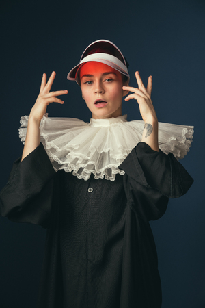 Look deeper and think more extensively. Medieval young woman in black vintage clothing and red cap as a nun standing on dark blue background. Trying on new accessories. Concept of comparison of eras.