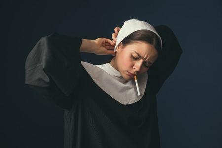 Preparation for the routine. Medieval young woman as a nun in vintage clothing and white mutch standing on dark blue background. Smoking cigarette in secret. Concept of comparison of eras.