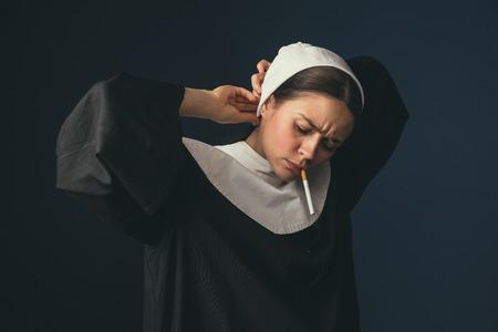 Vorbereitung auf die Routine. Mittelalterliche junge Frau als Nonne in Vintage-Kleidung und weißem Mutch, die auf dunkelblauem Hintergrund steht. Rauchen heimlich Zigarette. Konzept des Vergleichs von Epochen. Standard-Bild
