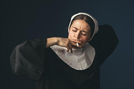 Jeden Tag das gleiche. Mittelalterliche junge Frau als Nonne in Vintage-Kleidung und weißem Mutch mit langen Haaren auf dunkelblauem Hintergrund. Rauchen heimlich Zigarette. Konzept des Vergleichs von Epochen.