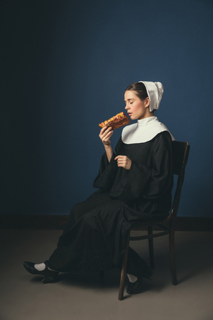 Last seconds before revelation. Medieval young woman as a nun in vintage clothing and white mutch sitting on the chair on dark blue background. Eating hot dog. Concept of comparison of eras.