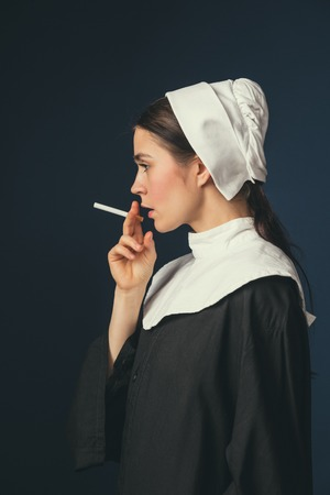 Flawless badass. Medieval young woman as a nun in vintage clothing and white mutch with long hair standing on dark blue background. Smoking cigarette in secret. Concept of comparison of eras.