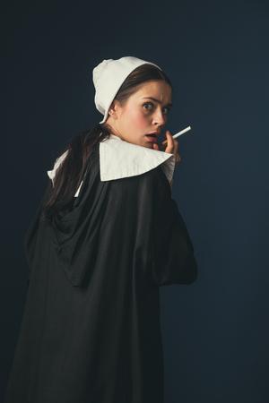 Mostra il tuo personaggio migliore. Giovane donna medievale come suora in abiti vintage e mutch bianco con capelli lunghi in piedi su sfondo blu scuro. Fumare sigaretta in segreto. Concetto di confronto di epoche.