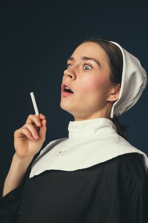 How can it be. Medieval young woman as a nun in vintage clothing and white mutch with long hair standing on dark blue background. Smoking cigarette in secret. Concept of comparison of eras. Banque d'images