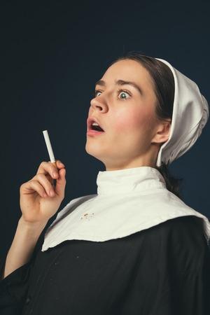 Wie kann es sein. Mittelalterliche junge Frau als Nonne in Vintage-Kleidung und weißem Mutch mit langen Haaren auf dunkelblauem Hintergrund. Rauchen heimlich Zigarette. Konzept des Vergleichs von Epochen.