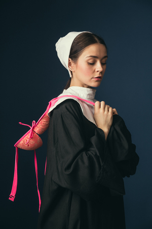 Serious innocent approach to spree. Medieval young woman in black vintage clothing and mutch as a nun standing on dark blue background. Trying on bright pink bra. Concept of comparison of eras.