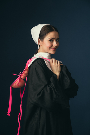 Flexibility of modernity and new features. Medieval young woman in black vintage clothing as a nun standing and smiling on dark blue background. Trying on pink bra. Concept of comparison of eras. Banco de Imagens