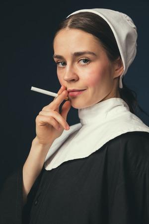Rebellische Jugend. Mittelalterliche junge Frau als Nonne in Vintage-Kleidung und weißem Mutch mit langen Haaren auf dunkelblauem Hintergrund. Rauchen heimlich Zigarette. Konzept des Vergleichs von Epochen.