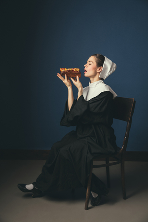 The moment of the truth - now or never. Medieval young woman as a nun in vintage clothing and white mutch sitting on the chair on dark blue background. Eating hot dog. Concept of comparison of eras.