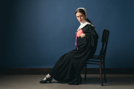 Bereit, Helligkeit im grauen Tag hinzuzufügen. Mittelalterliche junge Frau in schwarzer Vintage-Kleidung als Nonne, die auf dem Stuhl auf dunkelblauem Hintergrund sitzt. Anprobieren eines neuen rosa BHs. Konzept des Vergleichs von Epochen.