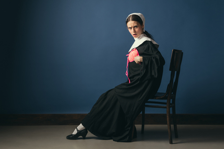 Ready to add brightness in gray day. Medieval young woman in black vintage clothing as a nun sitting on the chair on dark blue background. Trying on new pink bra. Concept of comparison of eras.