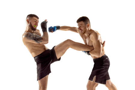Decisive moment. Two professional fighters posing isolated on white studio background. Couple of fit muscular caucasian athletes or boxers fighting. Sport, competition and human emotions concept.