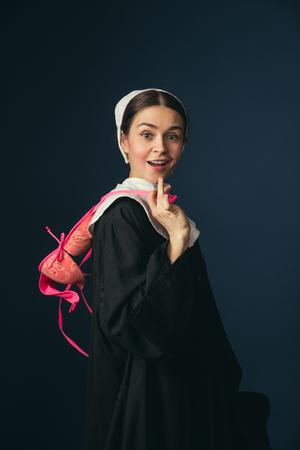 Preguntándose por nuevas sensaciones de conveniencia y comodidad. Mujer joven medieval en ropa vintage negra como monja de pie sobre fondo azul oscuro. Probándose sujetador rosa. Concepto de comparación de eras.