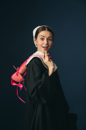 Wondering of new feelings of convenience and comfort. Medieval young woman in black vintage clothing as a nun standing on dark blue background. Trying on pink bra. Concept of comparison of eras.