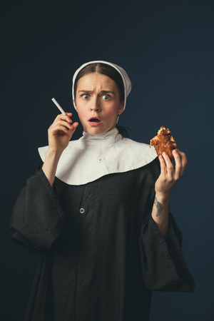 Problems of taboo. Medieval young woman as a nun in vintage clothing sitting on the chair on dark blue background. Smoking cigarette and eating hot dog in secret. Concept of comparison of eras.