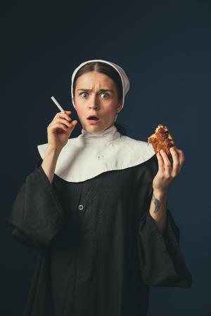 Tabuprobleme. Mittelalterliche junge Frau als Nonne in Vintage-Kleidung, die auf dem Stuhl auf dunkelblauem Hintergrund sitzt. Zigarette rauchen und heimlich Hot Dog essen. Konzept des Vergleichs von Epochen.