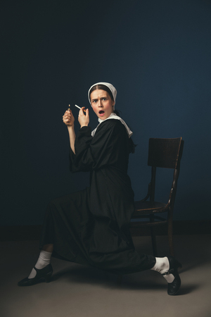 Protect your rights of chilling. Medieval young woman as a nun in vintage clothing and mutch sitting on the chair on dark blue background. Smoking cigarette in secret. Concept of comparison of eras.